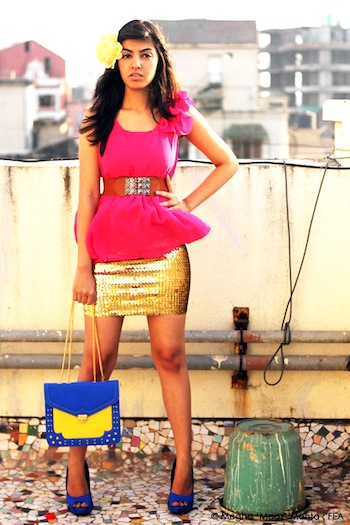 Bubble gum pink top, kept high-waisted with a gold sequined skirt. A yellow-blue satchel to match the blue tall heels and a yellow flower hair-clip to complete the look