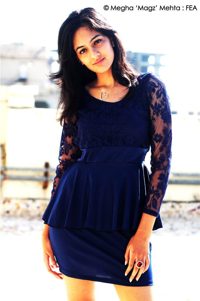 Blue short dress with a formal cut. Lace sleeves and neckline, neckpiece and ring complete the look.