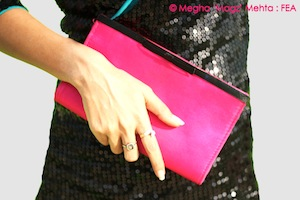 A hot pink clutch from my wardrobe, that has a satin ribbon and border on the opening side of it